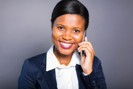 pretty african businesswoman making a phone call on plain background photo