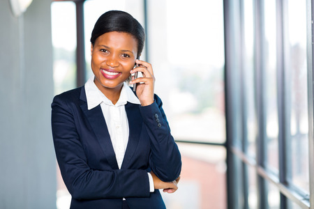 attractive african businesswoman talking on cell phone in office photo