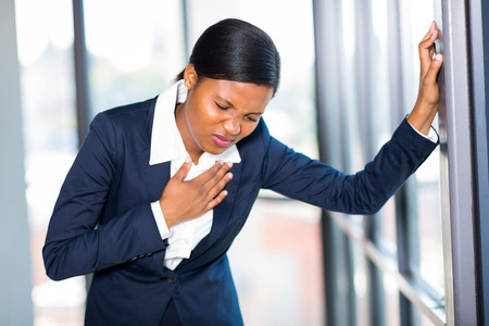 young african american businesswoman having heart attack or chest pain photo