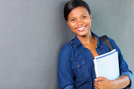 adult learning: pretty young african university girl standing against the wall
