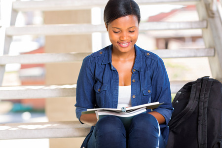smart african american university student reading a book outdoors photo