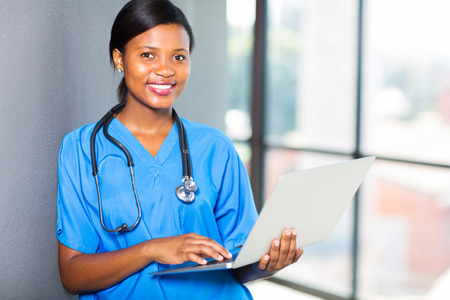 cute african healthcare worker using laptop at work