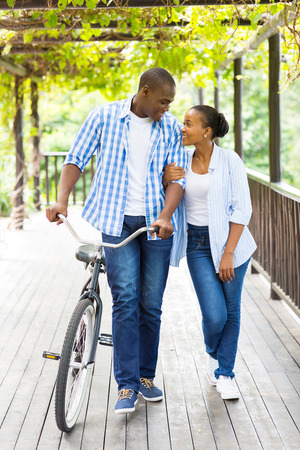young african american couple walking with bicycle under grape vines photo
