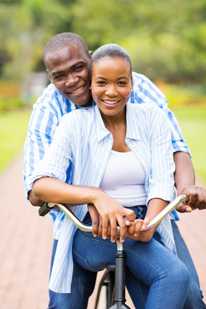 young african couple riding bicycle photo