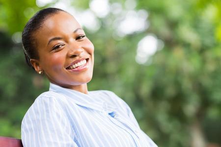 mujeres sentadas: negro mujer despreocupada joven sentado en el parque