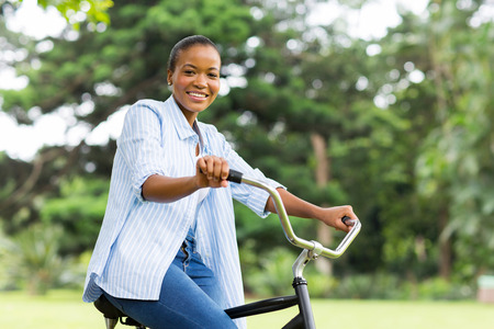 beautiful afro american woman riding bicycle in forest photo