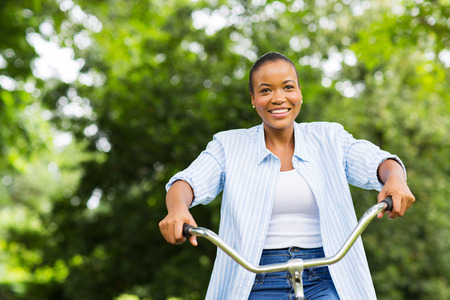 pretty young african american woman riding a bike in forest photo