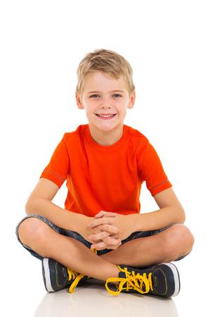 niños sentados: niño adorable que se sienta en el suelo aislado en fondo blanco Foto de archivo