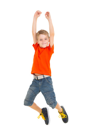 cheerful little boy jumping on white background Stock Photo