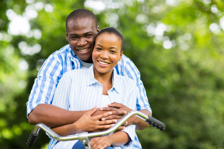 happy african couple on one bike relaxing in forest photo