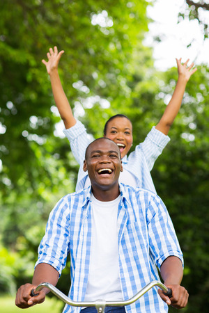 cheerful african girl having fun riding a bicycle with boyfriend photo