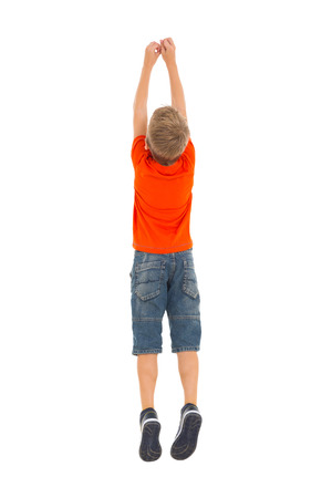 hang body: rear view of young boy jumping isolated on white background