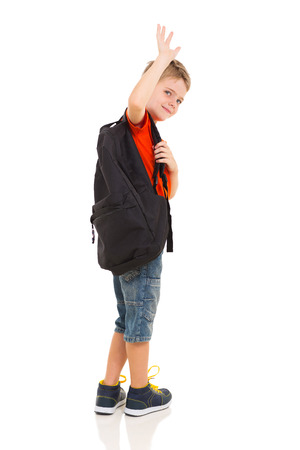 male elementary school student waving goodbye isolated on white background