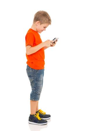 zijaanzicht van kleine jongen met behulp van tablet-pc op wit wordt geïsoleerd