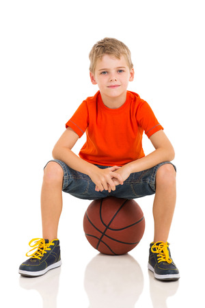 cute kid sitting on a basketball isolated on white photo