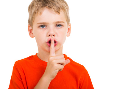 little boy doing silence gesture over white background