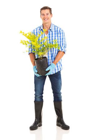 gardening gloves: full length portrait of man holding a plant