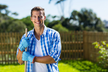 garden tool: handsome young man cleaning home garden