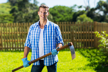 hoe: young man with a hoe in his home garden Stock Photo