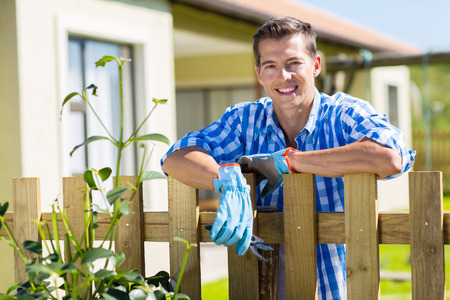 young man leaning against fence relaxing after doing some garden work in backyard photo