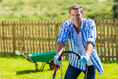happy man mowing lawn at home garden photo