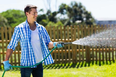 man in jeans: cheerful man watering home garden