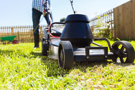 low angle view of man mowing his house garden lawn photo