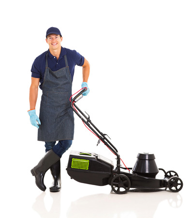 happy gardener standing next to a lawnmower isolated on white photo