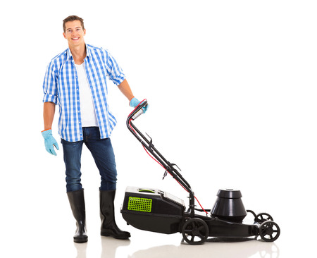 good looking man: good looking man standing next to an electric lawnmower on white background