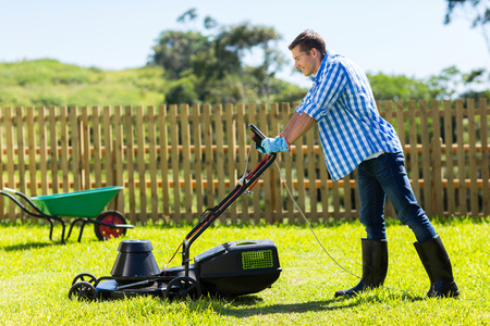 young man mowing lawn at home photo