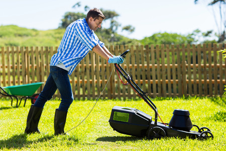 lawn mowing: cute man mowing lawn in the backyard of his house