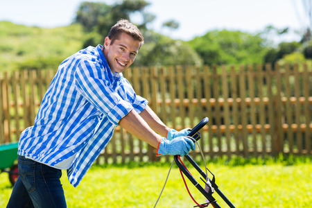 mowing grass: handsome young man pushing lawnmower in home garden