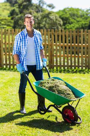 young man pushing wheelbarrow full of grass after cleaning backyard photo