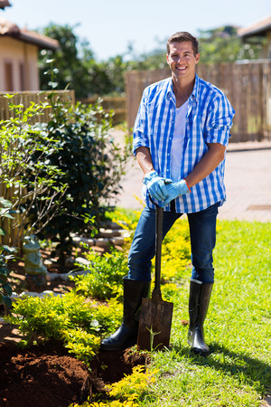happy young man with a spade in home garden photo