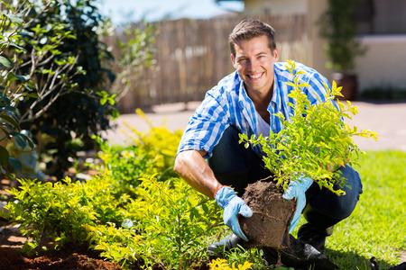 jardineros: hombre joven feliz jardinería en el patio trasero Foto de archivo