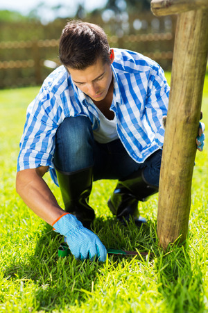 young man trimming grass at home garden photo
