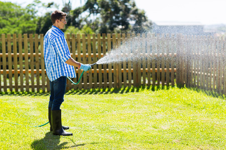 hosepipe: young man watering backyard lawn using hosepipe