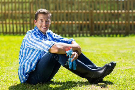 good looking man: good looking gardener sitting on lawn Stock Photo