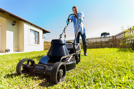 mowing grass: low angle view of young man mowing lawn at home Stock Photo