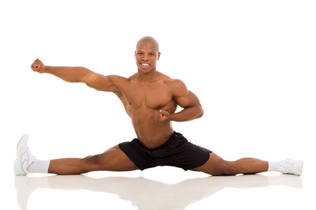 man working out: healthy young african american man splitting isolated on white background