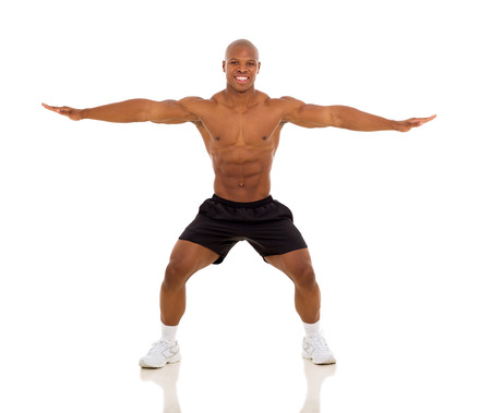 fit african man exercising and stretching on white background photo