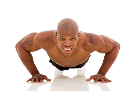 fit young African man doing pushups on floor photo