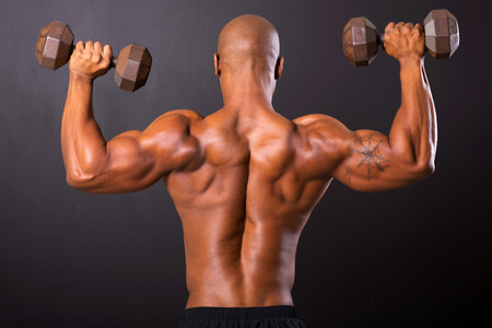 rear view of african bodybuilder training with dumbbells photo