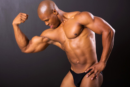 muscular african man posing on black background photo