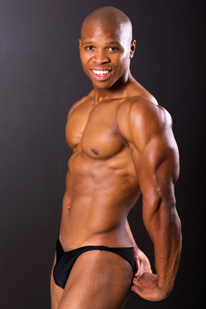 portrait of african male bodybuilder flexing muscles photo