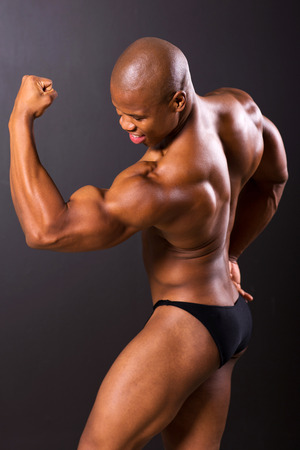 african muscular man showing muscles on black background photo