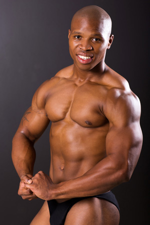 strong african american man flexing muscle over black background photo