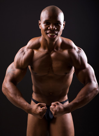 healthy african muscular bodybuilder posing on black background photo