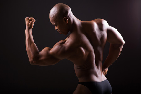 african american bodybuilder showing muscles on black background photo