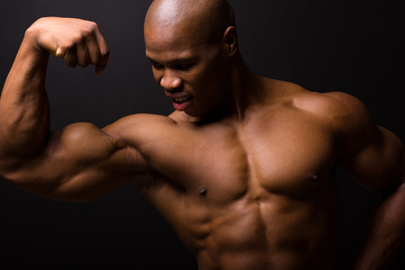 african muscular bodybuilder on black background photo